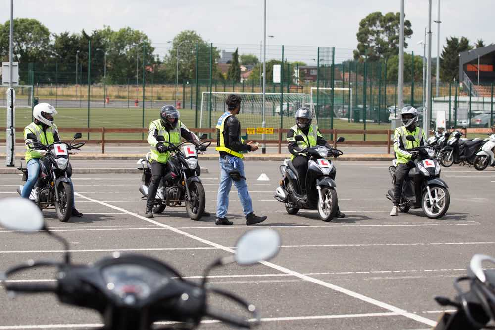 Four riders getting instruction in car park